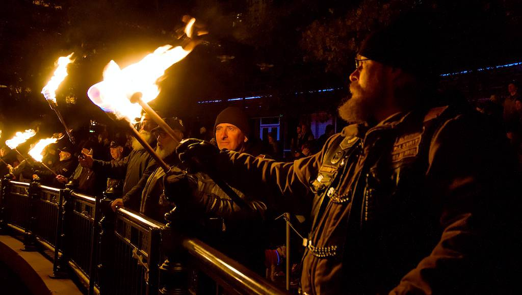 Torch bearers light their torches during the lighting ceremony. Photo by Jen Bonin.
